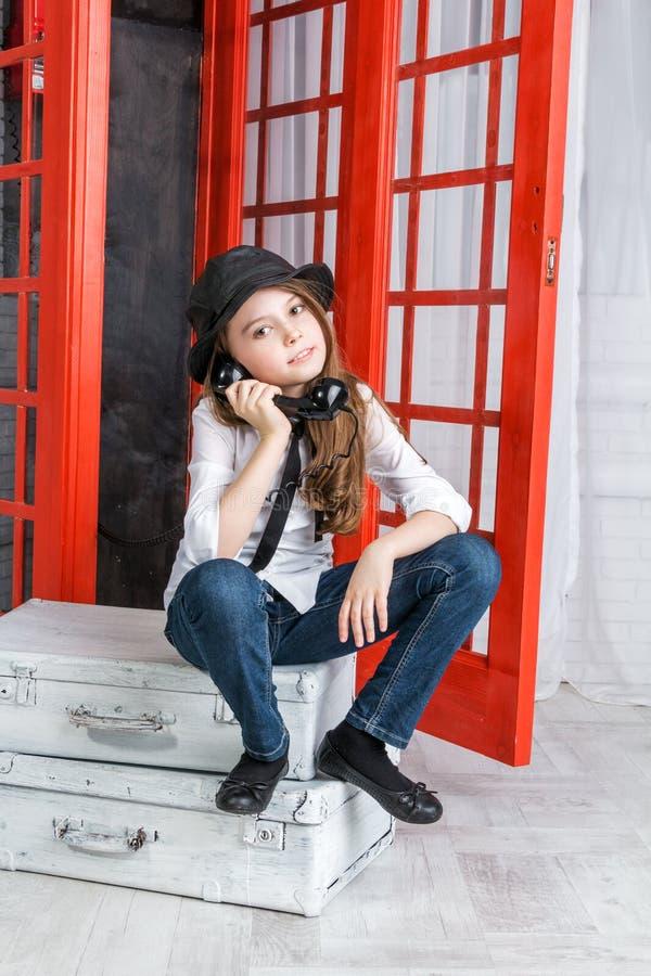 女孩坐手提箱在电话亭附近 免版税库存照片