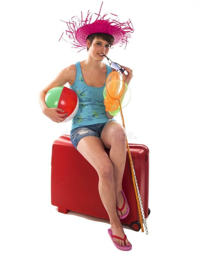 女孩坐手提箱等待 免版税库存照片