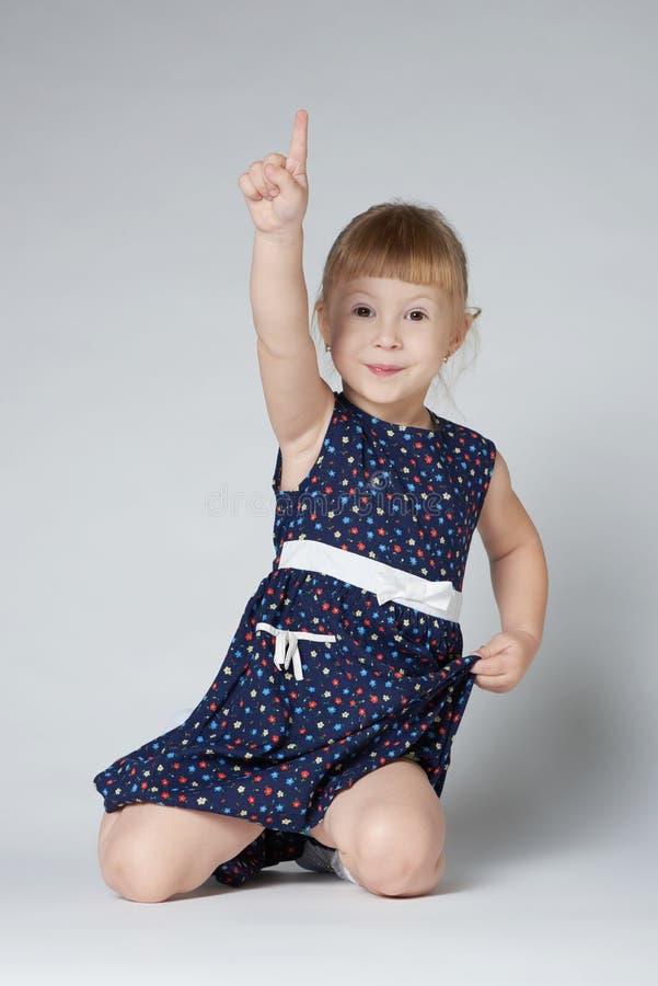 女孩坐指向的地板  免版税库存图片