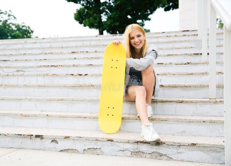 女孩坐有滑板的台阶 库存图片