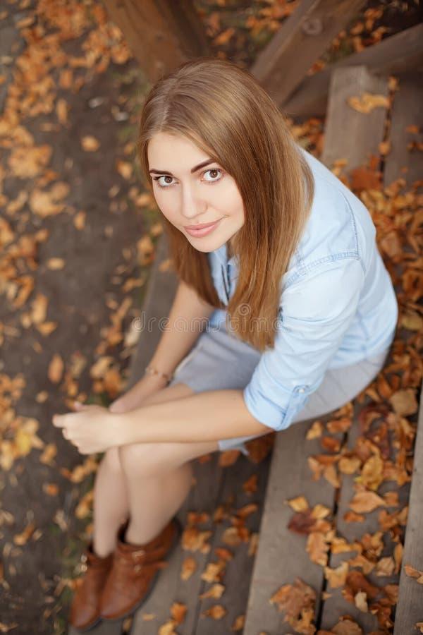 女孩坐木门廊的步,秋天季节 库存照片