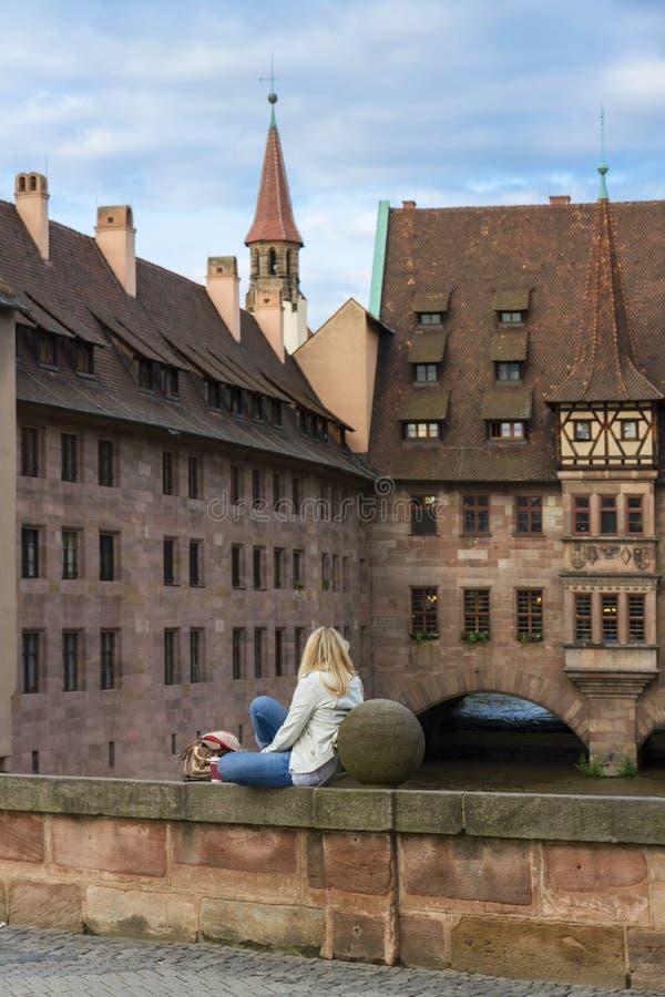 女孩坐横跨佩格尼茨河的一座石桥梁在纽伦堡 库存图片