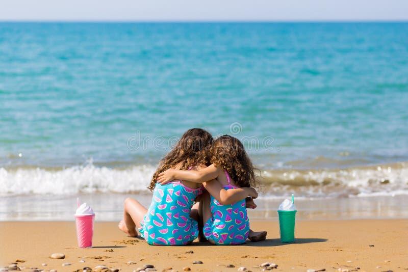 女孩坐沙子和拥抱,与鸡尾酒一起 家庭度假概念 愉快的姐妹 免版税库存照片