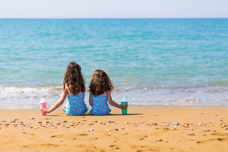 女孩坐沙子和拿着鸡尾酒 家庭度假概念 愉快的姐妹 免版税库存照片