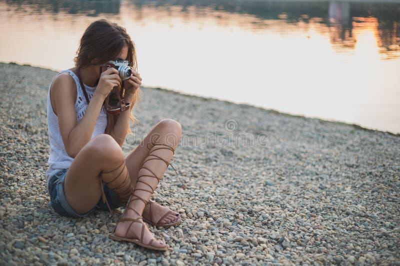 女孩坐海滩和拍摄 免版税库存图片