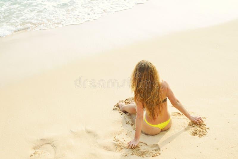 女孩坐热带海滩转动了渴望看天空 夏天海洋和沙子的妇女背景 顶视图 库存图片