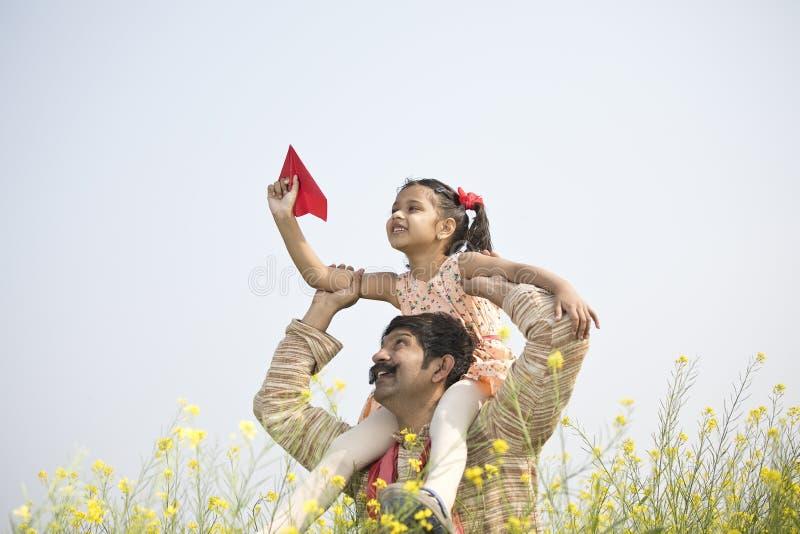 女孩坐父亲的肩膀和投掷的纸飞机 免版税库存图片