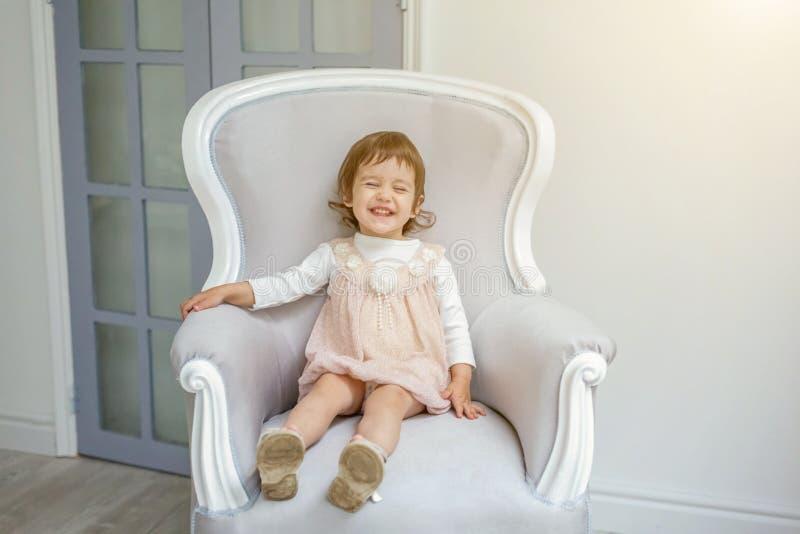 女孩坐现代椅子 免版税库存图片