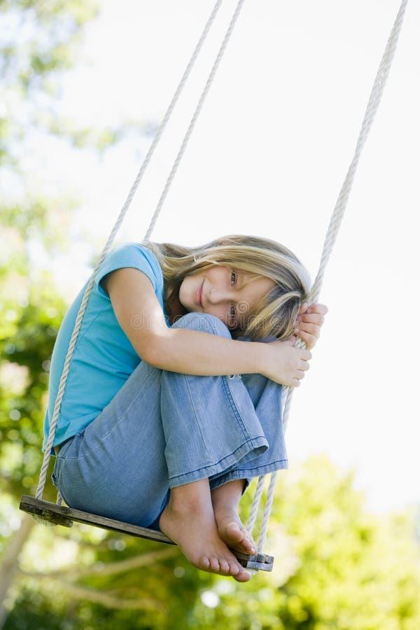 女孩坐的微笑的摇摆年轻人 免版税库存图片
