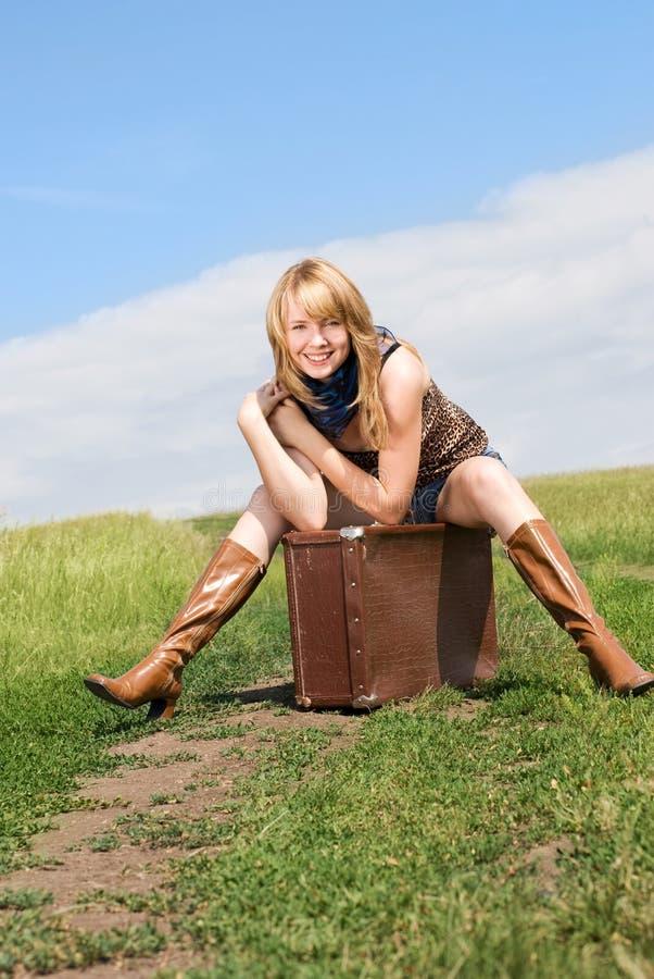 女孩坐的手提箱 免版税库存照片