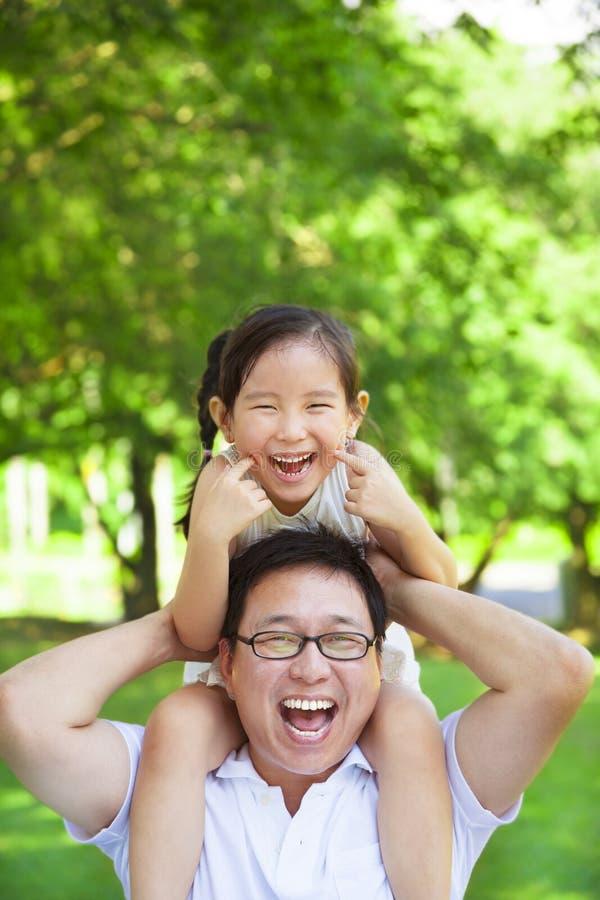 女孩坐的父亲肩膀和做一个滑稽的表情 库存图片