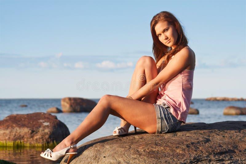 女孩坐的石年轻人 库存图片