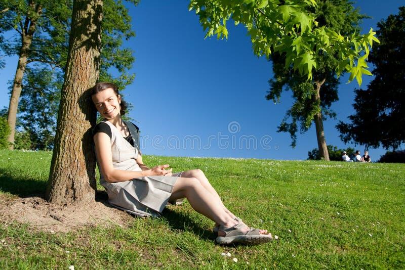 女孩坐的结构树下 免版税库存照片