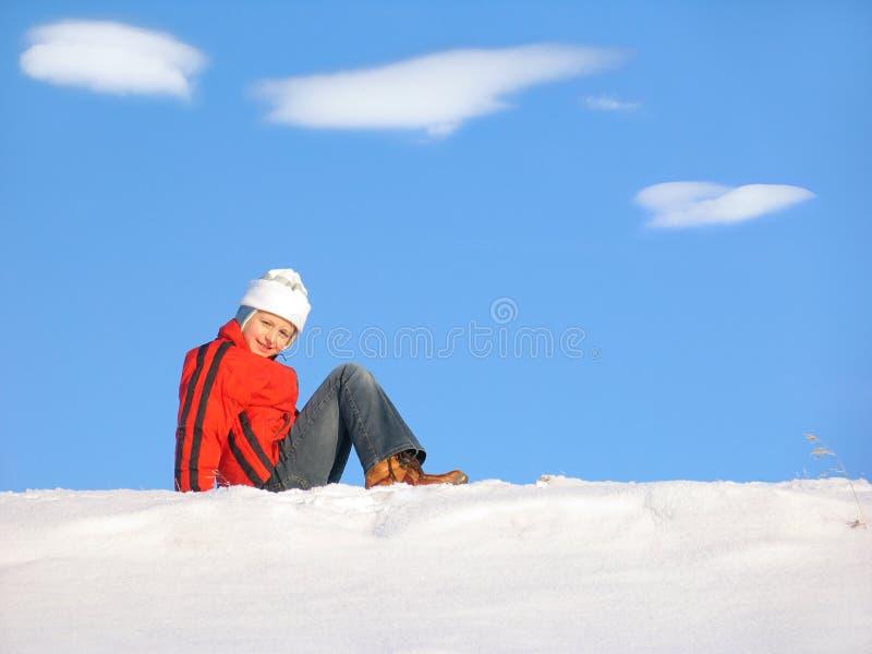 女孩坐的雪 免版税库存照片