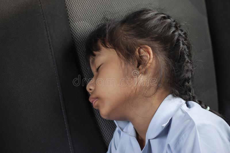 女孩坐睡着汽车一会儿去教育 免版税库存图片