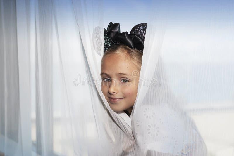 女孩坐窗口并且看从帷幕的后面 Stoks照片 图库摄影