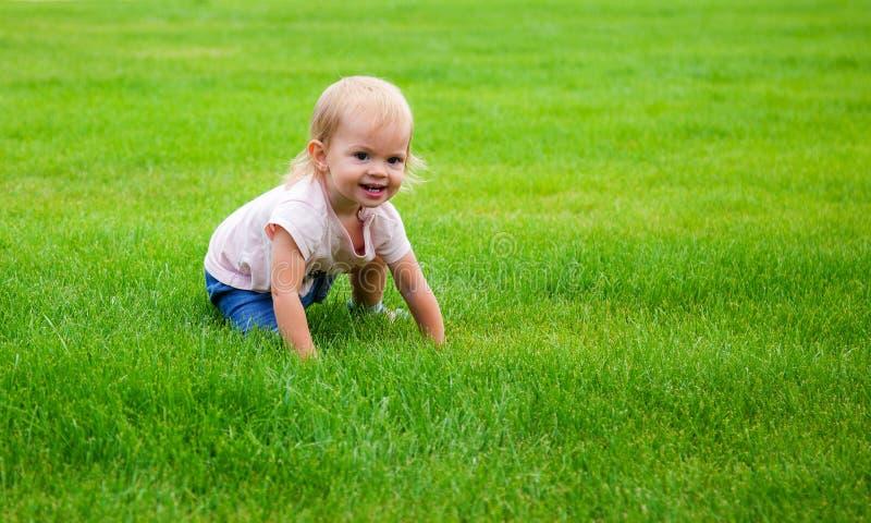 女孩坐绿草 图库摄影