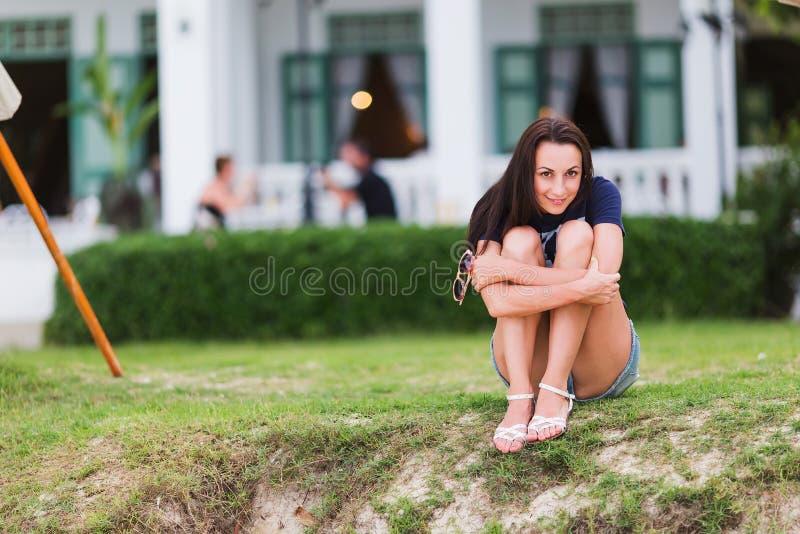 女孩坐草和微笑 库存图片