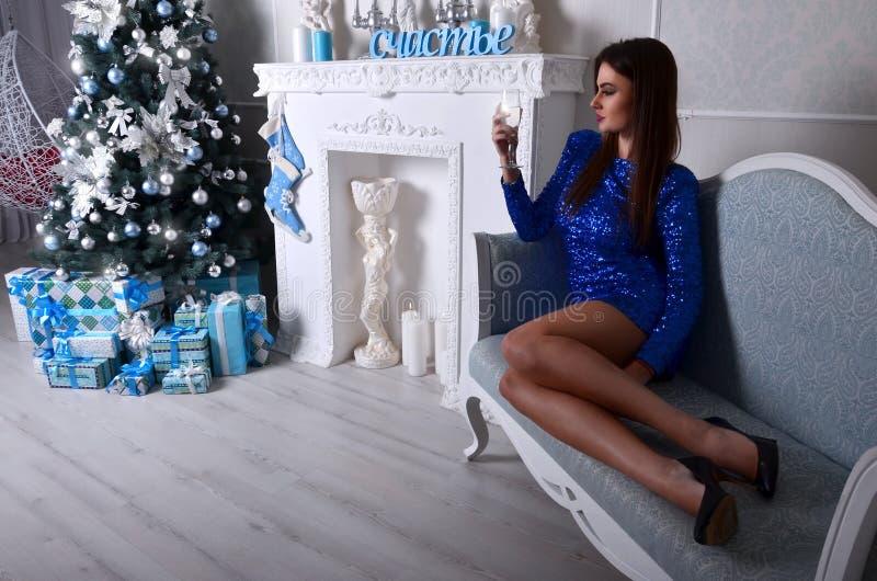 女孩坐蓝色长沙发 免版税图库摄影