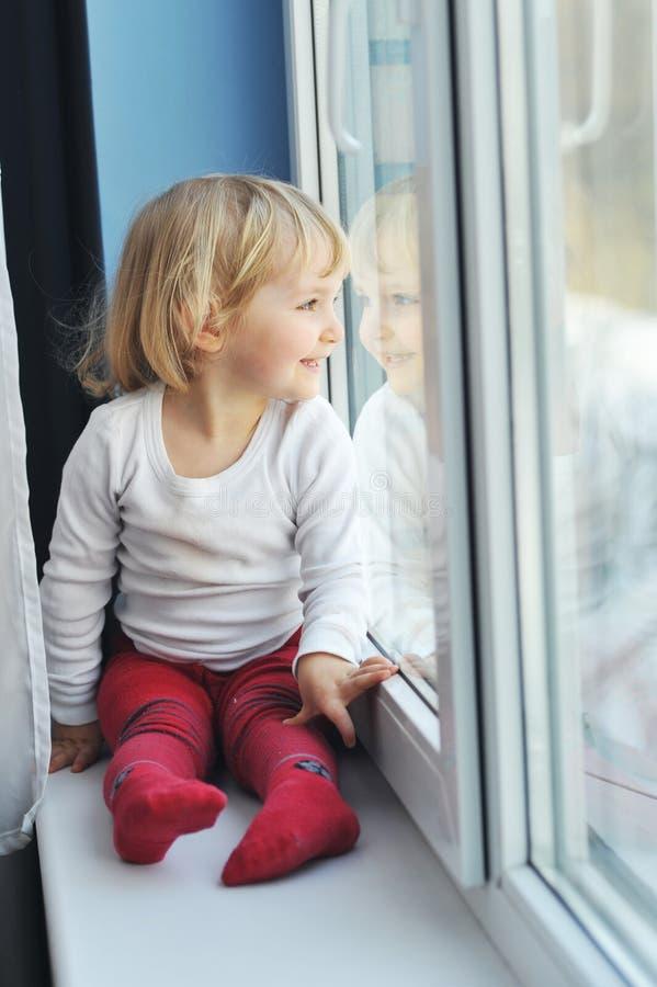 女孩坐视窗 免版税库存照片