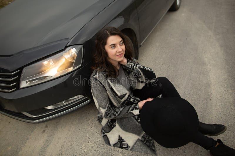 女孩坐路在一辆黑汽车附近 免版税库存照片