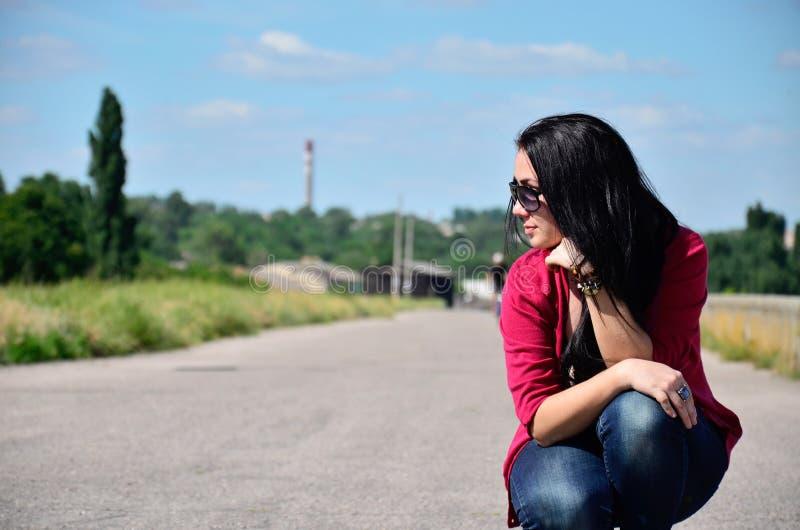 女孩坐路 免版税图库摄影