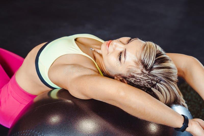 女孩坐锻炼的球 免版税库存图片