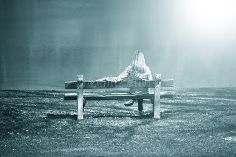 女孩坐长凳在水附近 库存照片