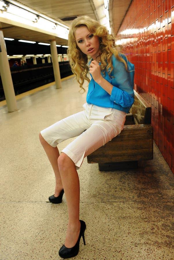 女孩坐长凳在空的地铁站 图库摄影