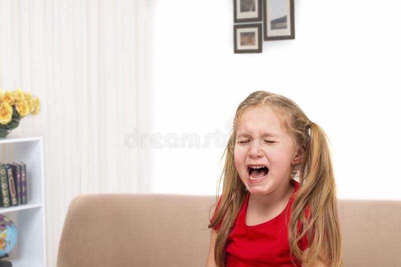 女孩坐长沙发和哭喊,放出在她的面颊下的泪花 库存图片