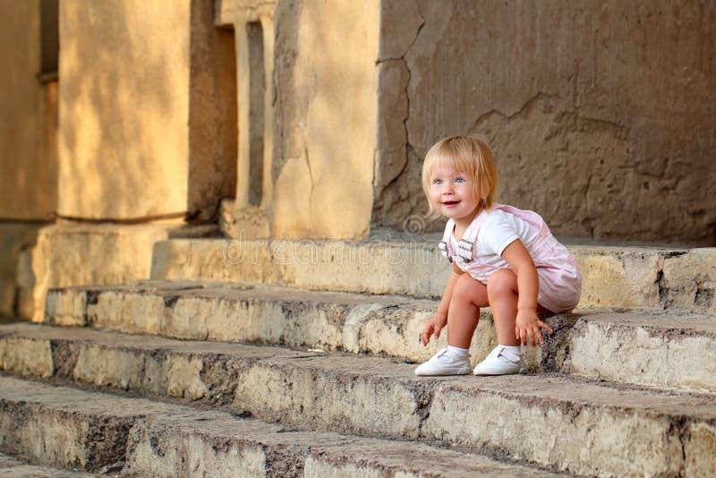 女孩坐门廊的步 免版税库存照片