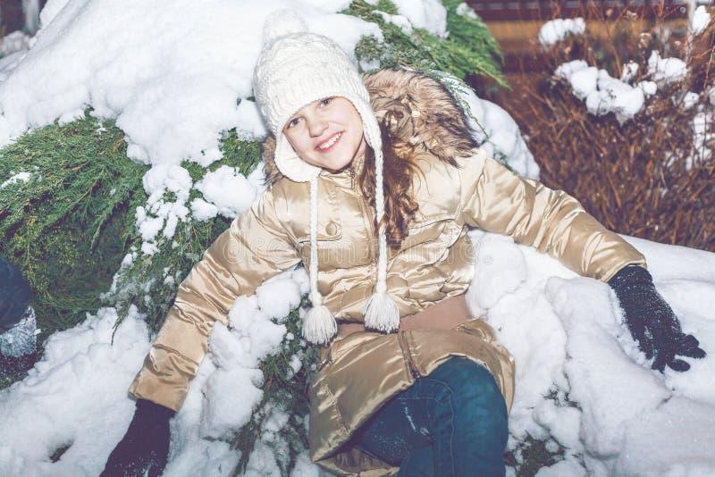女孩坐雪在晚上冬天森林里 免版税库存照片