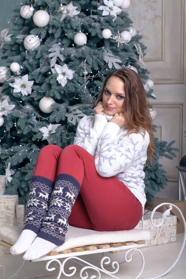 女孩坐雪撬,佩带一温暖的sweate 库存图片