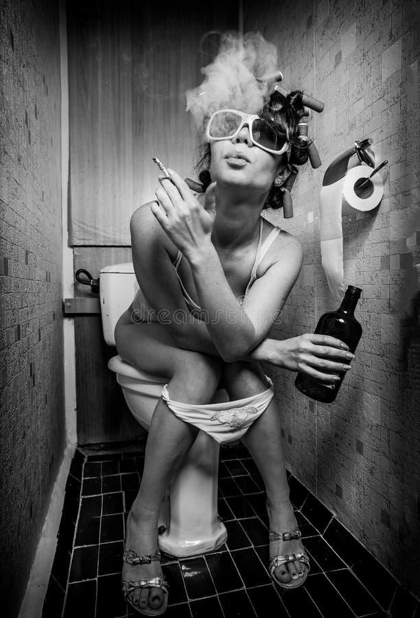 女孩坐洗手间 库存照片