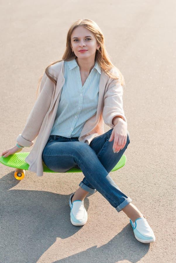 女孩坐滑板 图库摄影