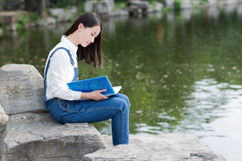 女孩坐读的湖 免版税库存图片