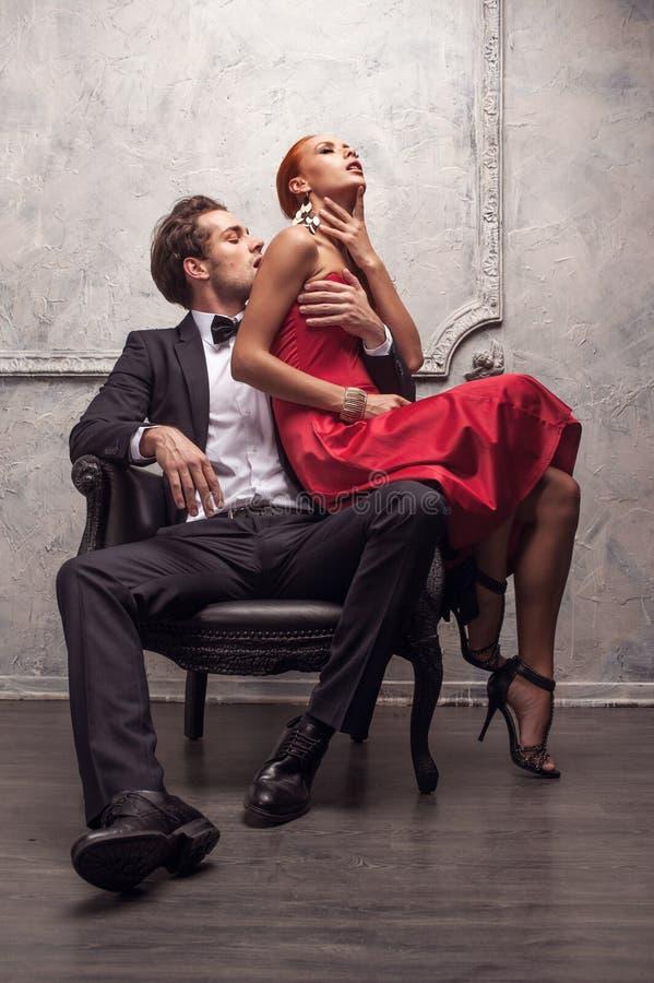 女孩坐他的膝盖 免版税库存照片
