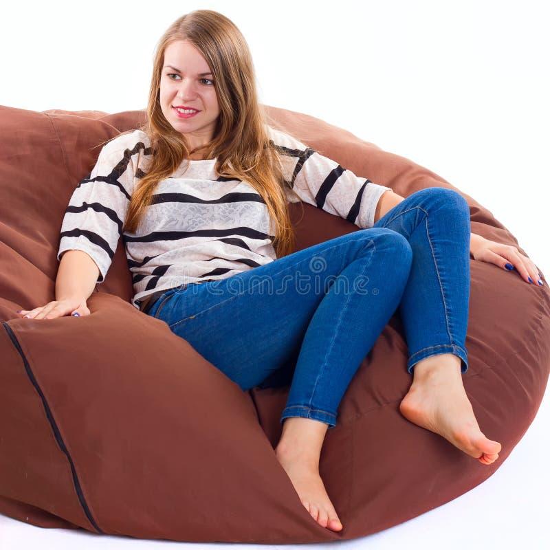 女孩坐braun装豆子小布袋椅子 库存图片