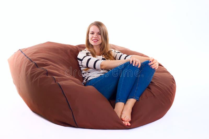 女孩坐braun装豆子小布袋椅子 免版税库存照片