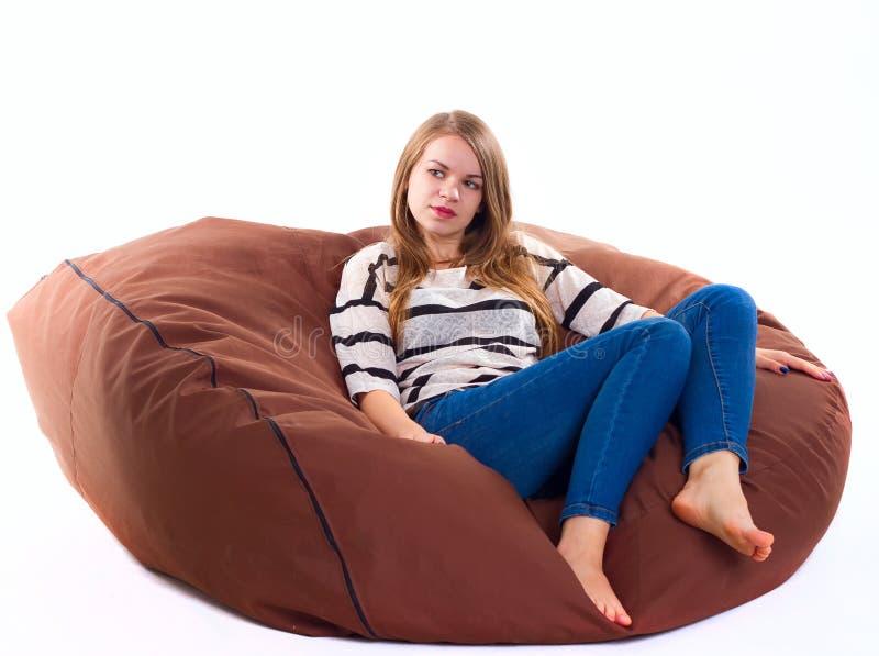 女孩坐braun装豆子小布袋椅子 免版税图库摄影