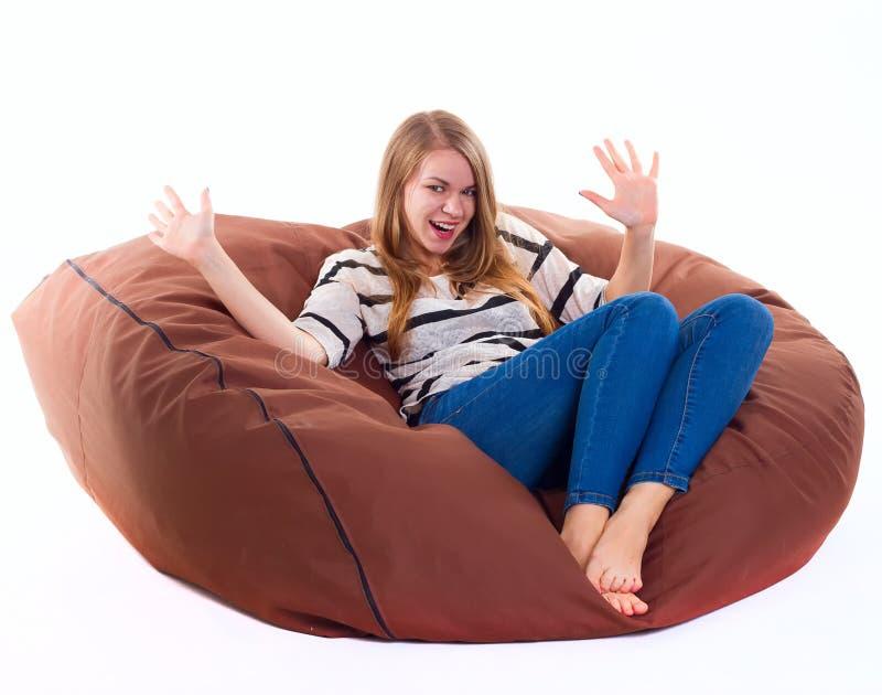 女孩坐braun装豆子小布袋椅子 库存照片