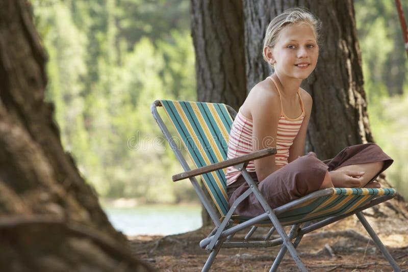女孩坐Deckchair在森林里 图库摄影