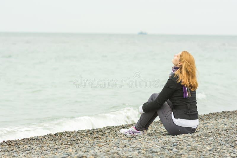 女孩坐Pebble海滩由海面孔对海风在一多云天 免版税库存照片