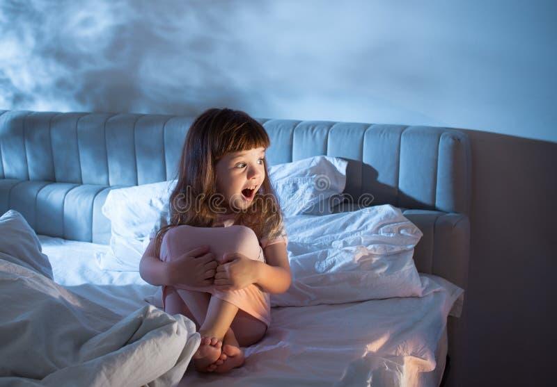 女孩夜时呼喊,当坐床 免版税库存照片