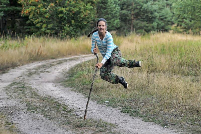 女孩奔跑和跃迁与藤茎 图库摄影