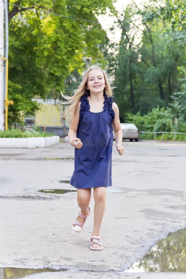 女孩奔跑在与被弄乱的头发的夏天 库存图片