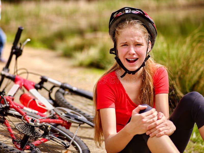 女孩女孩跌下自行车 骑自行车者女孩保留被挫伤的膝盖的自已 库存照片