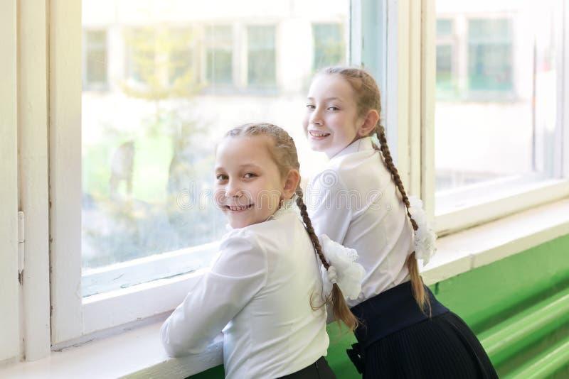女孩女小学生看窗口入街道 免版税图库摄影