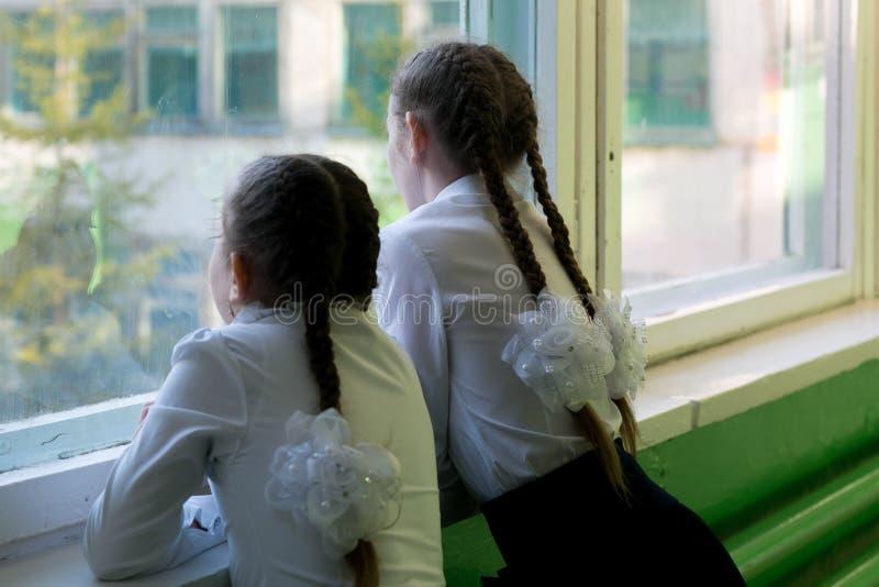 女孩女小学生看窗口入街道 免版税库存图片