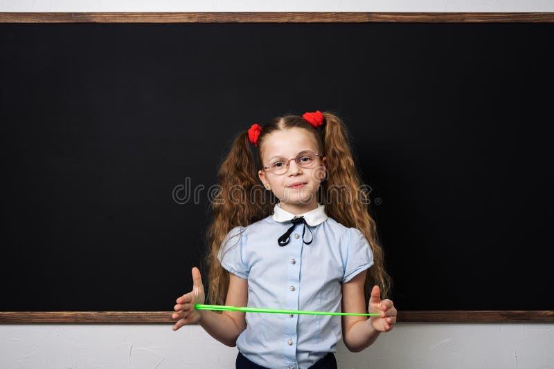 女孩女小学生站立在校务委员会并且拿着尖 库存图片